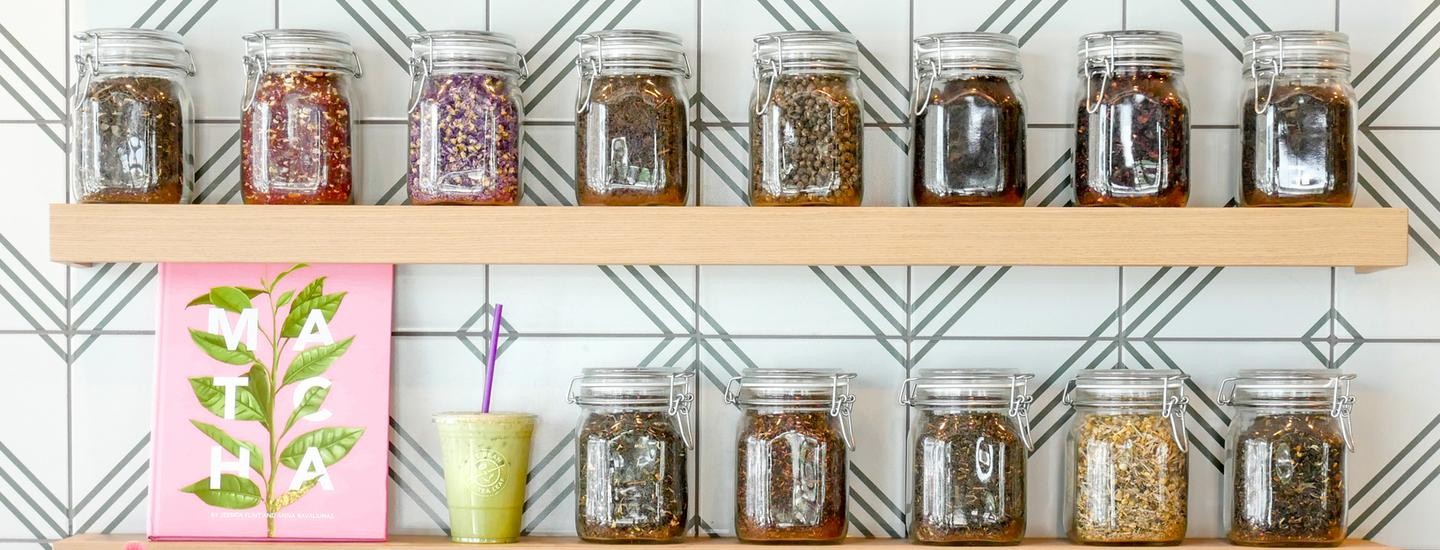 teas from around the world in glass jars on a shelf