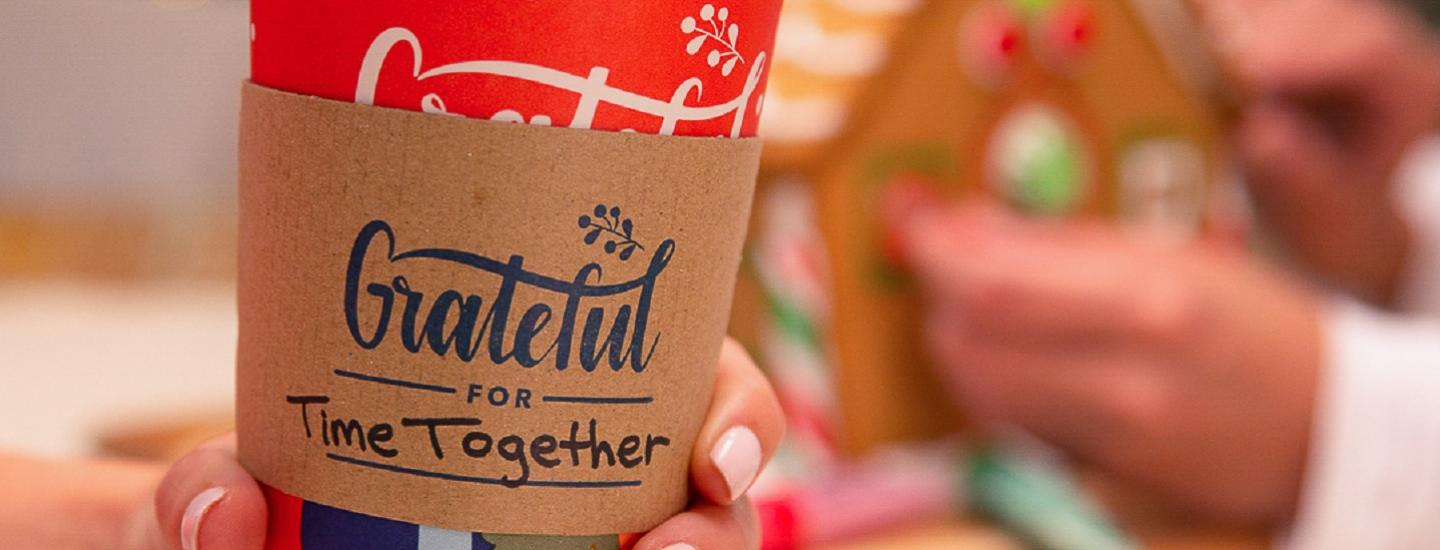 "holding our grateful holiday cup with the words ""grateful for downtime"" written on it"