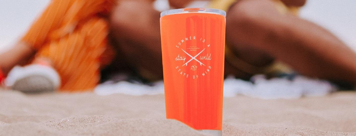 how to be more sustainable- featuring an orange tumbler on the beach