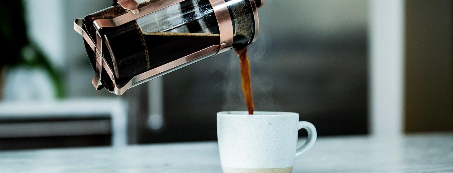 coffee brewed being poured into a white mug