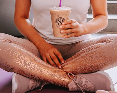woman holding iced coffee about to go to the gym
