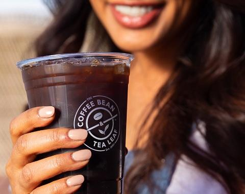 woman holding a coffee bean cold brew smiling