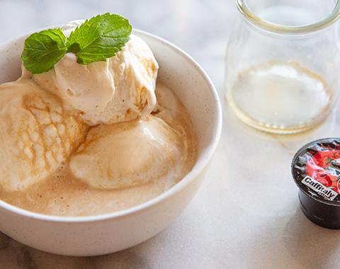 an affogato (a bowl of ice cream with espresso poured on top) on a kitchen counter, garnished with a sprig of mint