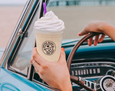 woman driving classic car with the top down, driving by the beach holding a vanilla ice blended drink