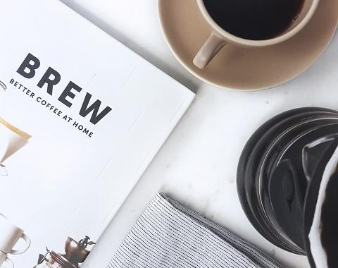 cup of coffee next to a brewing at home guide book