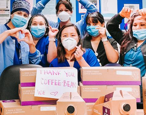 Healthcare workers with coffee and tea and 'Thank You Coffee Bean' sign