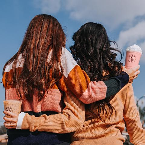 Two friends holding The Coffee Bean & Tea Leaf Valentine's Day Lattes